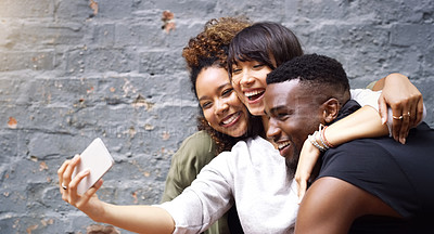Buy stock photo Shot of a group of friends taking a selfie together while posing outdoors against a grey brick wall