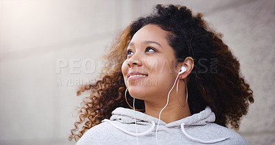 Buy stock photo Shot of an attractive young woman listening to music on her earphones while relaxing outdoors
