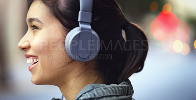 Buy stock photo Closeup shot of a cheerful young woman listening to music on her headphones while walking through the city