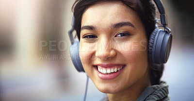 Buy stock photo Portrait of a cheerful young woman listening to music on her headphones while walking through the city