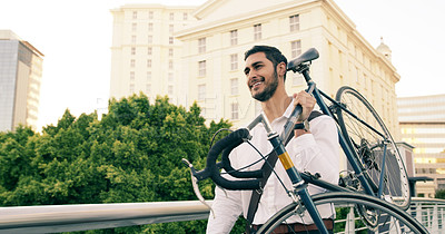 Buy stock photo Shot of a handsome young businessman carrying his bicycle on his shoulder while walking through the city