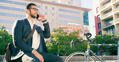 Buy stock photo Shot of a handsome young businessman taking a phone call while sitting down on some steps in the city