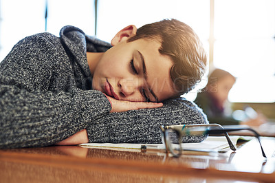 Buy stock photo Shot of an elementary schoolboy taking a nap in class