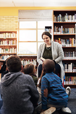 Buy stock photo Shot of a teacher reading to a group of elementary school kids in the library