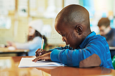 Buy stock photo Shot of an adorable elementary school boy working in class