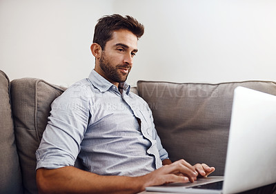 Buy stock photo Shot of a focused young man working on his laptop while being seated on a couch at home during the day