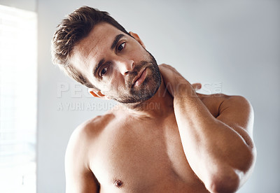 Buy stock photo Portrait of a handsome young man holding his neck in pain while relaxing at home