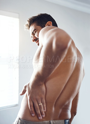 Buy stock photo Rearview shot of a shirtless young man holding his back in pain while relaxing at home
