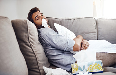 Buy stock photo Portrait of a sickly young man with a tissue up his nose siting on a couch and holding a pillow at home