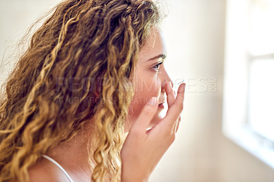 Buy stock photo Shot of an attractive young woman putting in her contact lenses at home