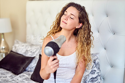 Buy stock photo Shot of an attractive young woman blowdrying her hair at home
