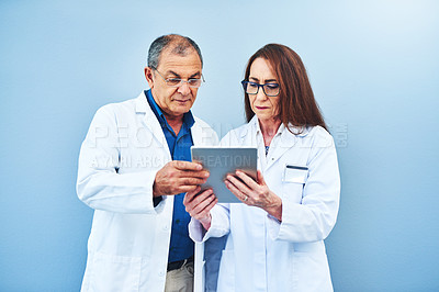 Buy stock photo Studio shot of two scientists using a digital tablet together against a blue background
