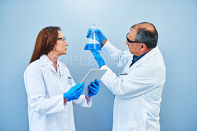Buy stock photo Studio shot of two scientists conducting an experiment while using a digital tablet against a blue background