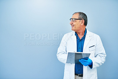 Buy stock photo Studio shot of a mature scientist writing on a clipboard against a blue background