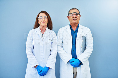 Buy stock photo Studio portrait of two scientists standing against a blue background