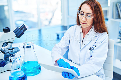 Buy stock photo Shot of a mature scientist using a digital tablet while working in a laboratory