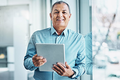 Buy stock photo Portrait of a mature businessman using a digital tablet in an office