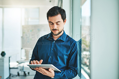 Buy stock photo Shot of a young businessman working on a digital tablet in an office