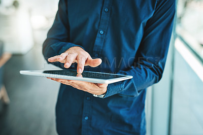 Buy stock photo Closeup shot of a businessman working on a digital tablet in an office