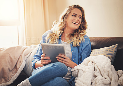 Buy stock photo Shot of a relaxed young woman using a digital tablet on the sofa at home