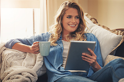 Buy stock photo Shot of a relaxed young woman having coffee and using a digital tablet on the sofa at home