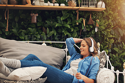 Buy stock photo Shot of a young woman using headphones with her smartphone while relaxing in the garden at home