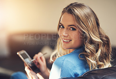Buy stock photo Shot of a relaxed young woman using a smartphone and stylus on the sofa at home