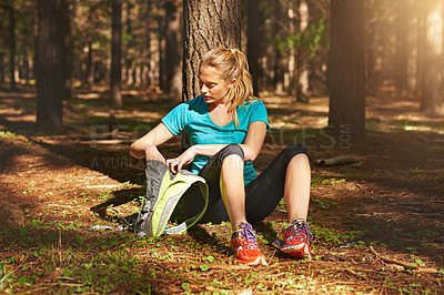 Buy stock photo Shot of a sporty young woman spending the day out in nature