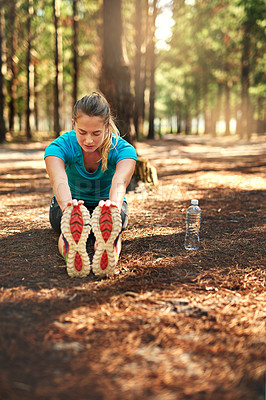 Buy stock photo Shot of a sporty young woman doing stretch exercise while out in nature