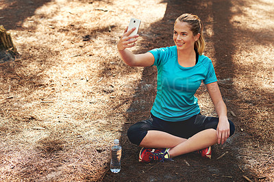 Buy stock photo Shot of a sporty young woman using her cellphone while out in nature