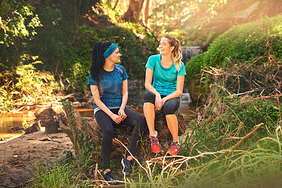 Buy stock photo Shot of two sporty young women taking a break while out exercising in nature