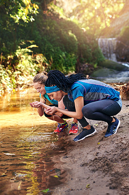 Buy stock photo Shot of two sporty young women drinking water from a water stream