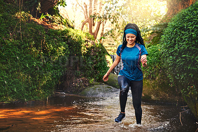 Buy stock photo Shot of a sporty young running through a stream of water in nature