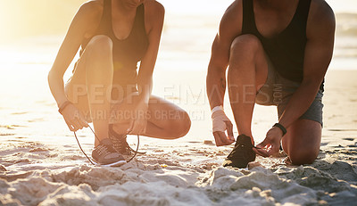 Buy stock photo Closeup shot of a couple tying their shoelaces while working out at the beach