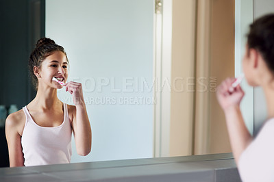 Buy stock photo Cropped shot of a teenage girl brushing her teeth in front of a mirror in the bathroom