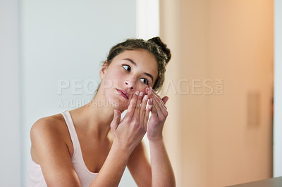Buy stock photo Cropped shot of a teenage girl squeezing a pimple in front of the bathroom mirror