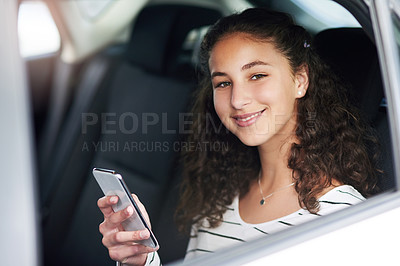 Buy stock photo Cropped portrait of a teenage girl using her cellphone while sitting in the backseat of a car