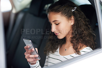 Buy stock photo Cropped shot of a teenage girl using her cellphone while sitting in the backseat of a car