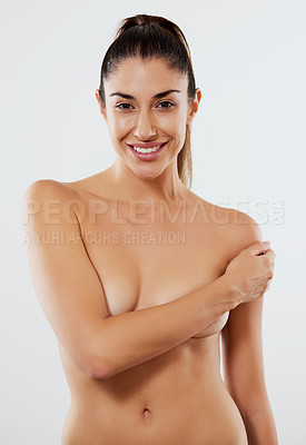 Buy stock photo Studio portrait of an attractive young woman covering her breasts while posing against a grey background