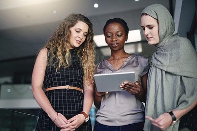 Buy stock photo Shot of a group of young businesspeople using a digital tablet in a modern office