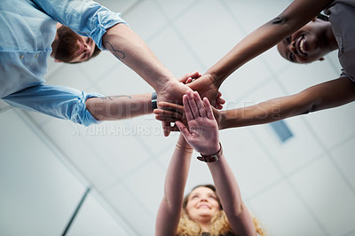 Buy stock photo Cropped shot of a group of colleagues joining their hands in solidarity in a modern office