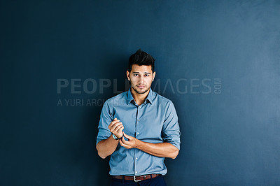Buy stock photo Studio portrait of a young businessman touching his wristwatch against a gray background
