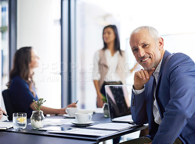 Buy stock photo Portrait of a businessman sitting in the office with his colleagues in the background