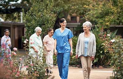 Buy stock photo Shot of a caregiver out for a walk with a group of senior women