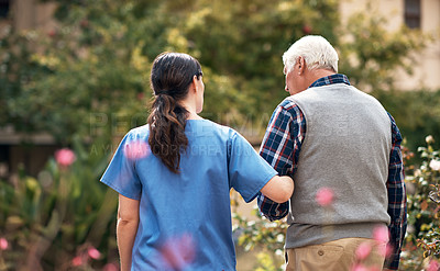 Buy stock photo Rearview shot of a caregiver and her patient out for a walk in the garden