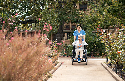 Buy stock photo Shot of a senior woman in a wheelchair out for fresh air in the garden with her caregiver