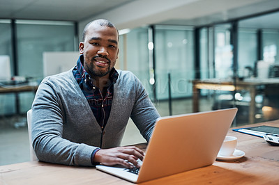 Buy stock photo Portrait of a handsome young businessman working on a laptop in his office