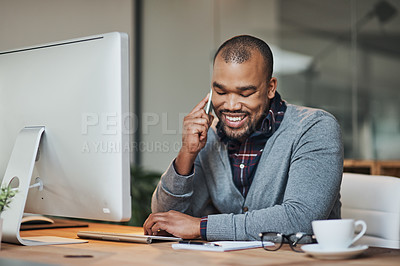 Buy stock photo Shot of a handsome young businessman taking a phone call on his cellphone while working in his office
