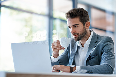 Buy stock photo Cropped shot of a handsome young businessman using a laptop and having coffee at his desk in a modern office