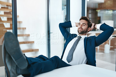 Buy stock photo Cropped shot of a handsome young businessman relaxing with his feet up on a desk in a modern office